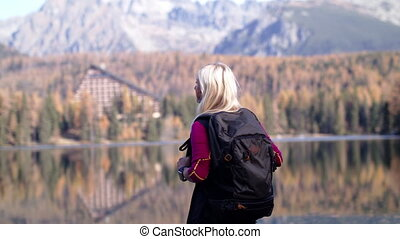 Active senior woman with backpack standing outdoors in nature, hiking.