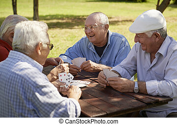 Active retirement, old people and seniors free time, group of four elderly men having fun and playing cards game at park. Waist up