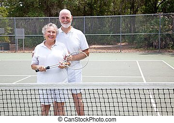 Active Seniors on Tennis Court - Portrait of active senior...