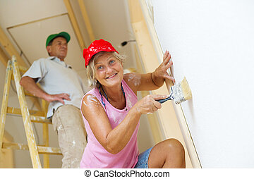 Active seniors painting wall - Active senior couple painting...