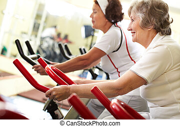 Active seniors - Two senior women exercising on training...