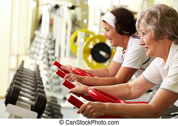 Active seniors - Two senior women exercising on training...
