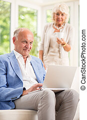 Active seniors with laptop