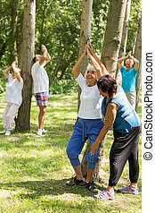 Active seniors working out in a garden