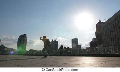 Active skateboarder doing kickflip trick outside - Skillful...