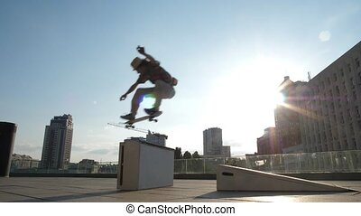 Active skater doing ollie trick jumping over curb - Young...