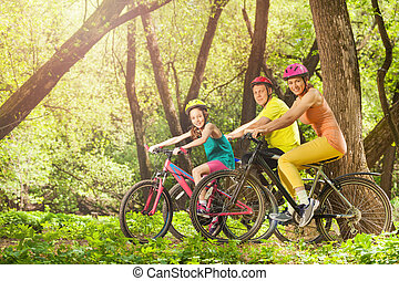 Active smiling family on bikes in the sunny forest