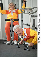 senior couple exercising in gym