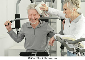 senior couple exercising in gym together