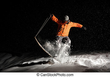 Active snowboarder in orange sportswear and mask jumping on a snowy hill at night