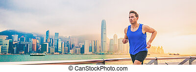 Active sport runner man jogging in Hong Kong city street living a healthy lifestyle training morning workout. Caucasian expat male athlete working out cardio banner panorama.