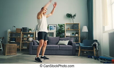 Active sportsman exercising at home rotating arms doing exercises for shoulders