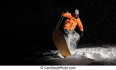 Active sportsman snowboarder in orange sportswear and mask jumping on a snowy hill at night