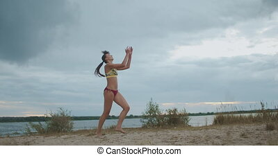 active sportswoman is playing beach volleyball, young and slender athlete is striking ball, slow motion shot, open court at nature
