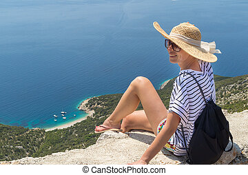 Active sporty woman on summer vacations sitting on old stone...