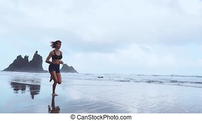 Active sporty woman run along ocean surf by water pool to...