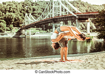 Active sporty young couple performing acroyoga asanas outdoors