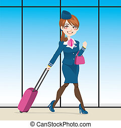 Beautiful stewardess walking through airport terminal carrying a hand purse and pull rod case