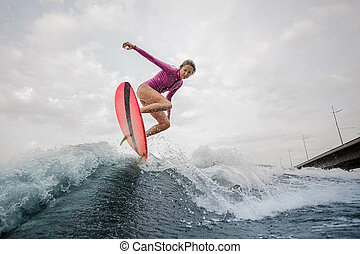 Active teenager girl jumping on the wakeboard