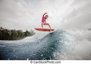 Active teenager girl riding on the wakeboard