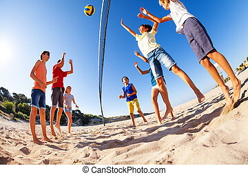 Active teens playing beach volleyball in summer