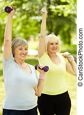 Active training - Vertical shot of elderly women doing...
