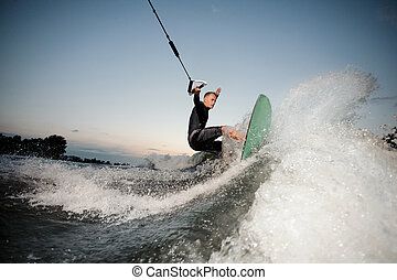 Active wakesurfer riding down the blue river high waves with splashes