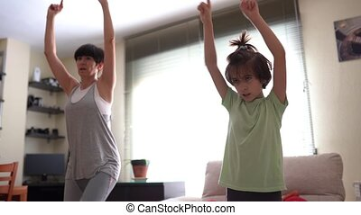 Active woman and cute daughter dancing in their living room at home.