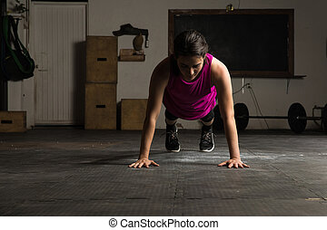 Active woman doing push-ups in a gym