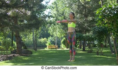 Active woman exercising using dumbbells in park
