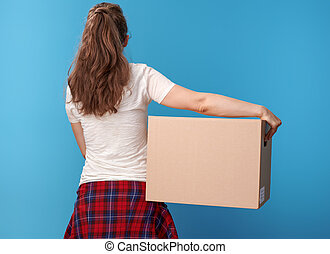 active woman in white shirt with cardboard box on blue