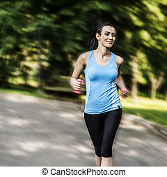 Active woman jogging with dumbbells