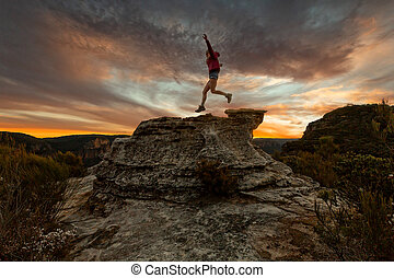 Active woman jumping on mountain cliffs at sunset