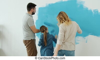 Active woman man and little girl are painting house walls renovating room and dancing having fun at home. Family lifestyle and accommodation concept.