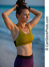active woman on ocean shore at sunset adjusting hair