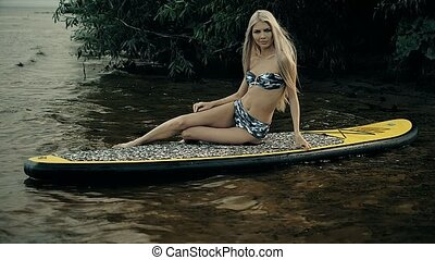 Active Woman Paddle Boarding On Summer evening - Active...