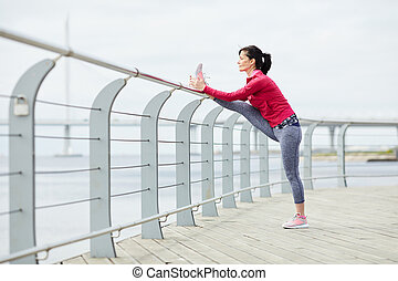 Active Woman Stretching on Pier