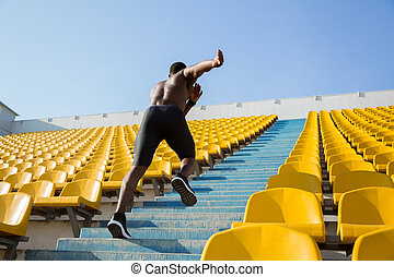 Active young african sportsman climbing up the stairs at the...
