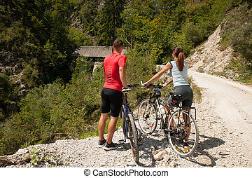Active young couple cycling in forest on a hot summer day
