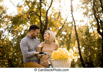 Active young couple enjoying romantic walk with bicycle in golden autumn park