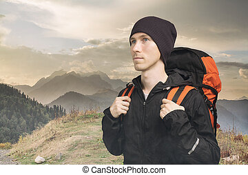Active young man hiking in the mountain, side view on cloudy landscape background. Active lifestyle and tourism.
