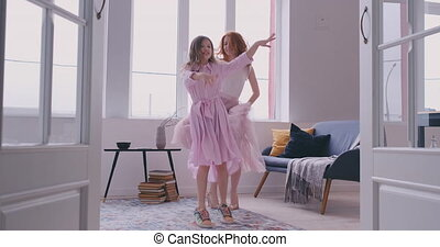 Active young mom babysiter and cute little kid daughter jumping dancing in modern house living room, happy family mother with child girl having fun enjoy playing funny activity together at home