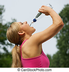 Active young woman drinking water after exercise