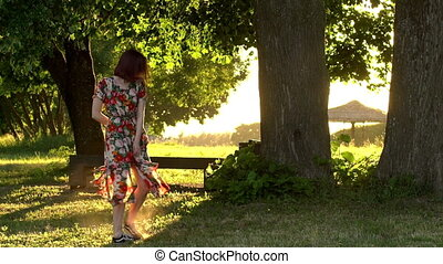 Active young woman in colorful dress turn on evening sunset...
