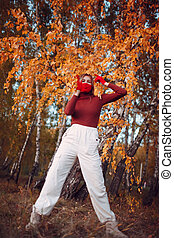 Active young woman in red gloves and face mask at autumn park