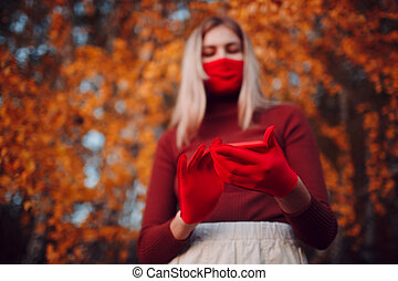 Active young woman in red gloves and face mask at autumn park with mobile phone