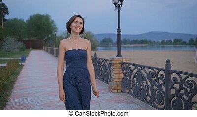 Active young woman is walking briskly, in the hands of her handbag golden brown.