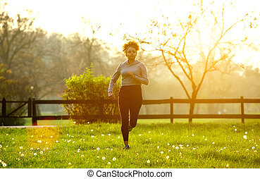 Active young woman running outdoors in nature