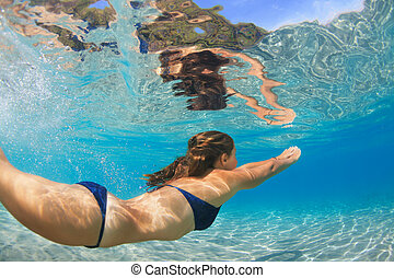Active young woman swim underwater in tropical blue lagoon