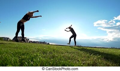 Active young women performs acrobatic stunts on the grass at summer sunset